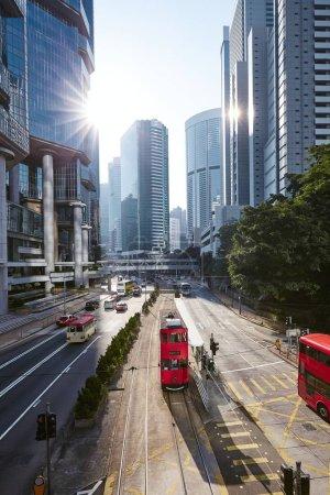 Photo pour Tram double étage rouge dans la rue de la ville contre gratte-ciel. Circulation dans la zone financière du centre-ville de Hong Kong, Chine. - image libre de droit