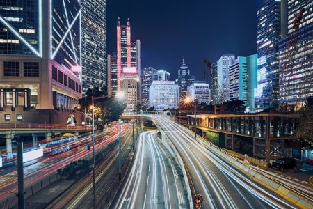 Photo pour Trafic achalandé dans la ville moderne. Sentiers lumineux de voitures contre les toits urbains nocturnes, Hong Kong . - image libre de droit