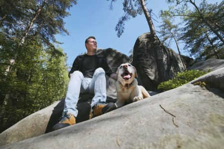 Man with his dog resting on rock in the middle of forest. Bohemian Paradise, Czech Republic