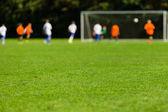 Rozmazané fotbalistů na zelené hřiště