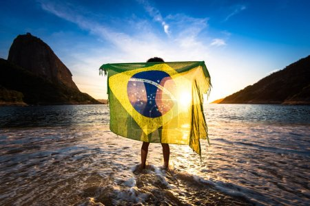 Photo for Girl With Curly Hair and Brazilian Flag on Her Back Standing in the Beach and Watching the Sunrise with the Sugarloaf Mountain in the Horizon, in Rio de Janeiro - Royalty Free Image