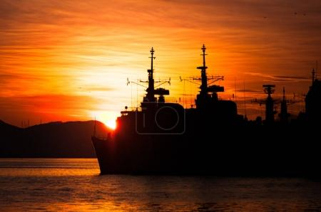 Silhouette of military navy ships at scenic sunset