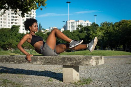 Young Attractive Fitness Woman Doing Knee Raise Crunch Exercise in the City Park on the Concrete Bench