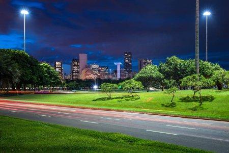 Carretera de cuatro carriles que cruza el parque Flamengo por la noche con senderos ligeros desde vehículos, y el centro de la ciudad de Río de Janeiro en el horizonte