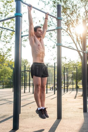 Young muscular athlete doing pull-up exercises