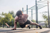 Athlete young man doing one-arm push-up exercise