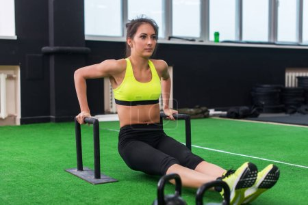 fit strong woman doing L-sits work-out in gym