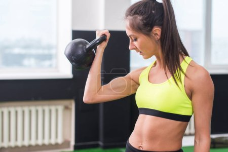 young fit woman doing exercises lifting kettlebell