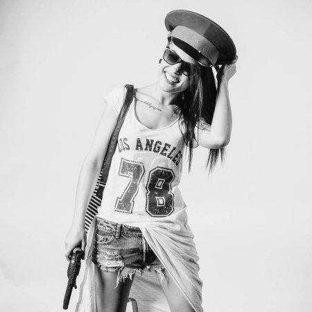 Photo pour Fille sexy de mode swag portant fusil femme s'amuser à porter police cap noir et blanc. - image libre de droit