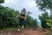 Fitness female athlete running on forest path