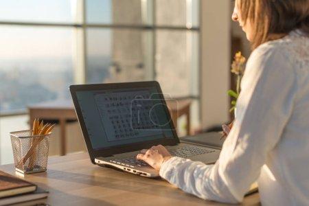 Photo pour Femme écrivaine tapant à l'aide d'un clavier d'ordinateur portable à son lieu de travail le matin. Femme écrivant des blogs en ligne, vue de côté image en gros plan - image libre de droit