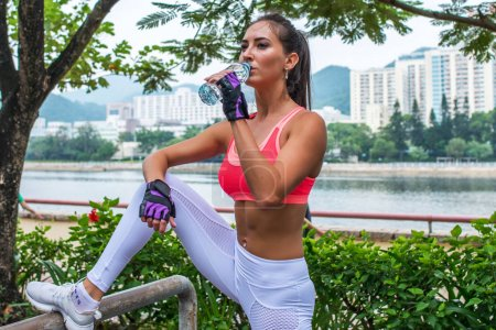 Sporty young female athlete taking a break after exercising or running