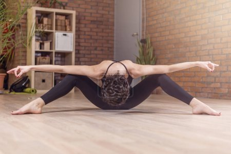 Professional dancer sitting facedown stretching