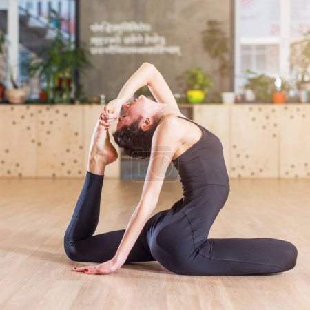 Woman working-out in studio doing stretching exercise