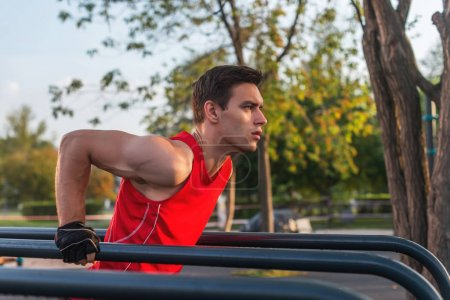 Fit man workout out arms on dips horizontal bars