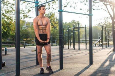 Fitnes man posing on street fitness station