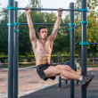 Athlete hanging on fitness station performing legs...