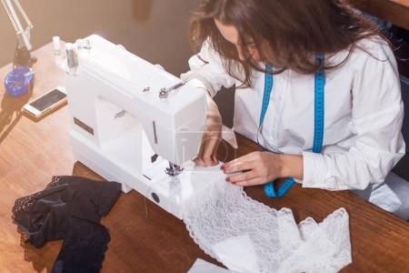 Young fashion designer stitching delicate lace