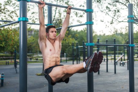 Photo for Young fitness man doing hanging leg raises exercise working out his abs in the park - Royalty Free Image