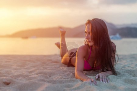 Attractive model lying on sandy beach
