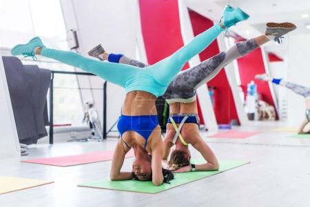 Girls working out together doing wide leg headstand, advanced yoga pose in modern fitness club
