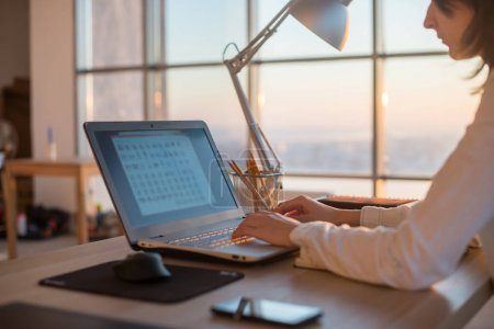 Photo for Side view photo of a female programmer using laptop, working, typing, surfing the internet at workplace - Royalty Free Image