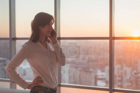 Young woman talking using cell phone at office in the evening. Female businesswoman concentrated, looking forward, calling by mobile device on her workplace.