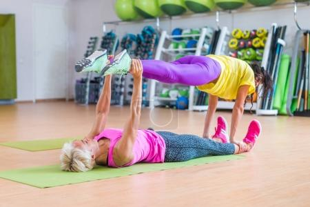 Two female fitness models doing yoga exercises, one lying on floor  mat holding legs of another above her in a sports center