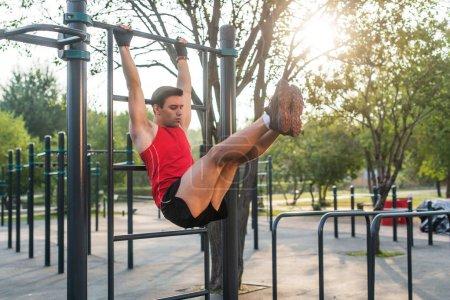 Photo pour Fitnes homme accroché sur des barres murales effectuant des jambes soulève. Entraînement transversal de base travailler les muscles abdominaux . - image libre de droit