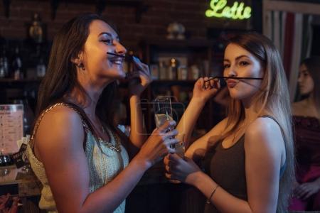 Photo pour Copines ayant une fête tenant des verres de cocktails, s'amuser, faire moustache avec de la paille dans la boîte de nuit . - image libre de droit