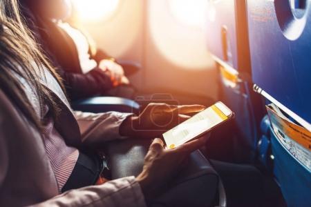 Photo pour Image du gros plan de mains féminines tenant smartphone assis dans l'avion. - image libre de droit