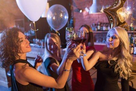 Foto de Grupo de hermosas niñas caucásico en vestidos elegantes sonriente bebiendo vino tostado celebrando el cumpleaños en un café. - Imagen libre de derechos