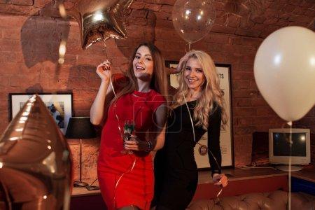 Photo pour Deux jolies femmes en robes de cocktail posant avec des ballons à la fête d'anniversaire dans un café élégant . - image libre de droit