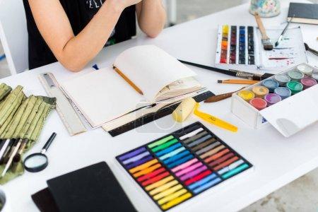 Photo pour Gros plan d'angle d'une femme peintre, dessin de projet au carnet de croquis à l'aide du crayon. Artiste esquisse dans le studio d'art avec l'ensemble de crayons de couleur - image libre de droit