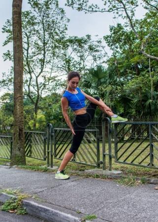 Photo pour Fille faire exercice d'étirement sur clôture dans le parc. Athlète féminine prépare pour entraînement matin ou faire du jogging en été - image libre de droit