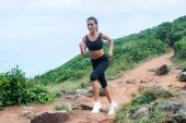 Fitness female athlete running on forest path in mountainous area in summer. Sporty woman working out going uphill.
