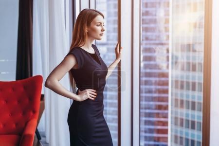 Mujer atractiva y acomodada pensando de pie en la ventana admirando el paisaje urbano en su apartamento ático