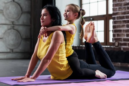 Photo pour Jeune femme caucasienne faisant des exercices d'étirement pour la colonne vertébrale avec un enfant assis sur son dos dans la salle de gym . - image libre de droit