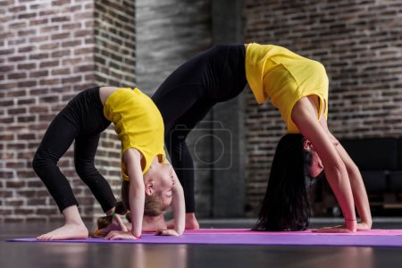 Photo for Kids yoga female teacher training a child girl standing in wheel pose working out in stylish sports studio. - Royalty Free Image