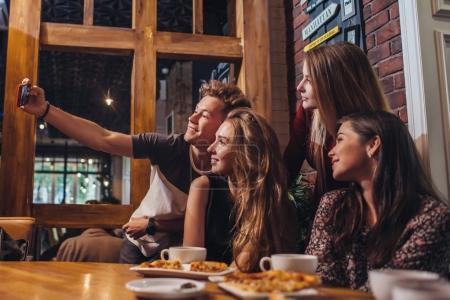 Photo pour Amis excités prenant selfie avec smartphone assis à la table ayant nuit dehors - image libre de droit