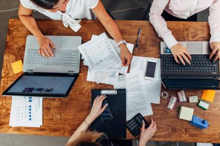Top view of three women working with documents using laptops sitting at desk