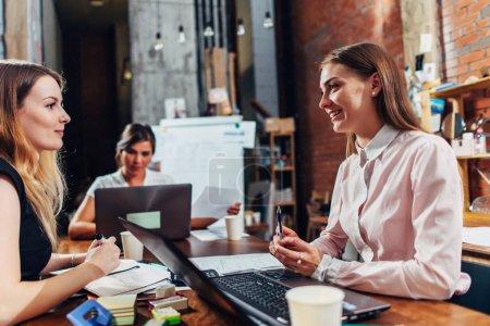 Photo pour Équipe de femmes d'affaires travaillant avec des papiers à l'aide d'ordinateurs portables assis au bureau . - image libre de droit