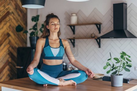 Sporty woman sits on a table with her eyes closed and meditates.