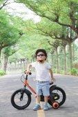Little boy riding a bike. Green Tunnel outdoor.