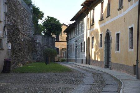 Foto de Orta San Giulio, Italia - Mayo, 23, 2019: grupos de turistas paseando por la calle del pueblo. - Imagen libre de derechos
