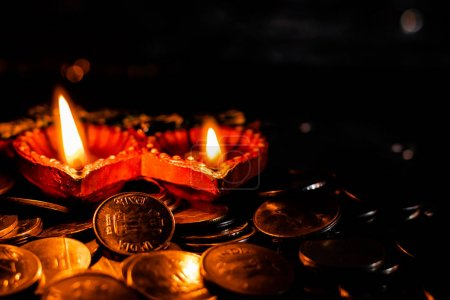 High angle shot of two glowing earthen lamps with coins against