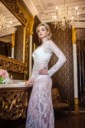 beautiful blonde young woman in white lingerie in a bathroom interior. bride's morning
