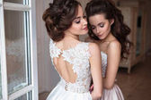 Beautiful bride and bridesmaids in luxury dresses. Twins young women in wedding photosession