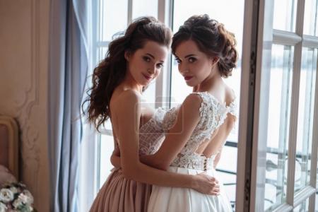 Photo pour Belle mariée et demoiselles d'honneur en robes de luxe. Jumeaux jeunes femmes en photosession de mariage - image libre de droit