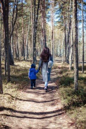 Photo pour Petit garçon marche dans une forêt printanière avec sa mère - image libre de droit